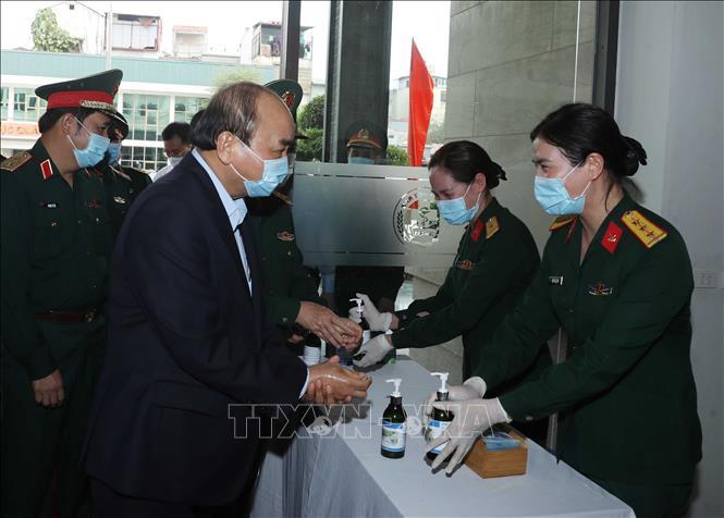Thủ tướng Nguyễn Xuân Phúc rửa tay sát khuẩn trước khi vào họp. Ảnh: Thống Nhất/TTXVN