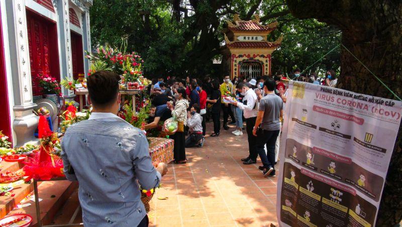 Thông báo phòng chống virus SARS-CoV-2 và dịch COVID-19 ngay tại đền, chùa, nhưng người dân vẫn tập trung rất đông tại Phủ Tây Hồ dâng lễ.