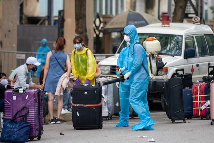 Cán bộ y tế phun khử trùng toàn bộ hành lý của những người từ vùng dịch về, trước khi làm thủ tục vào khu cách ly.