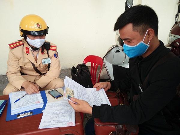 Đại úy Đỗ Xuân Khoa, Tổ trưởng tổ xử lý Đội cảnh sát giao thông số 6 vừa xử lý lỗi vi phạm giao thông vừa kết hợp tuyên truyền, hướng dẫn người dân về hình thức nộp phạt trực tuyến
