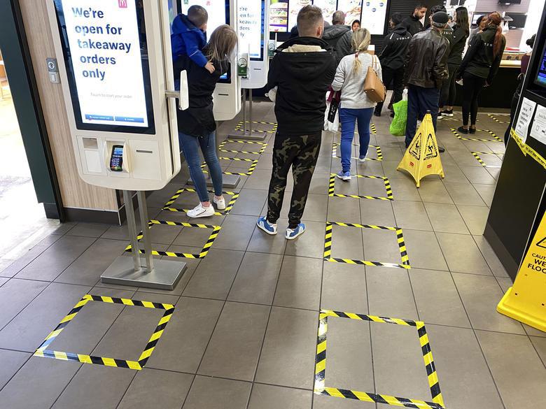 Người dân Anh xếp hàng theo ô đứng chỉ định tại Trung tâm mua sắm Brent Cross ở thủ đô London.