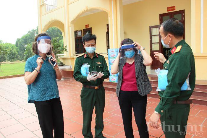 Các đồng chí trong Trung đoàn pháo binh 58 chia sẻ với chị em cán bộ Hội LHPN Hà Nội về sản phẩm kính chắn giọt bắn do đơn vị tự sáng chế, phục vụ công tác phòng dịch Covid-19.