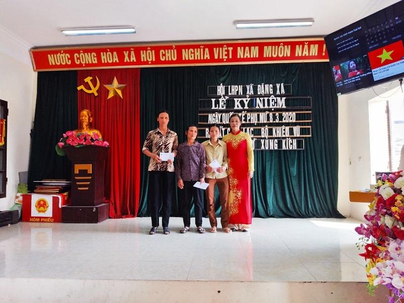 : Chị Ngô Thị Hồng Huệ, Chủ tịch Hội LHPN xã Đặng Xá (áo đỏ đứng thứ 2 từ bên trái sang) trao tặng sổ tiết kiệm cho gia đình hội viên có hoàn cảnh khó khăn.