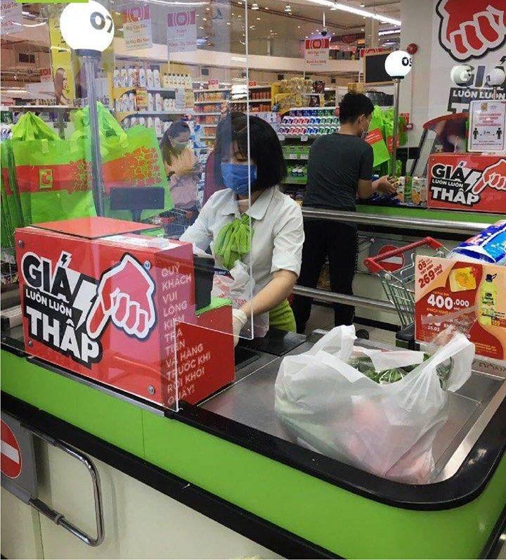 Tấm kính trong được lắp đặt tại quầy thu ngân của siêu thị để ngăn ngừa nguy cơ lây truyền bệnh qua tiếp xúc gần