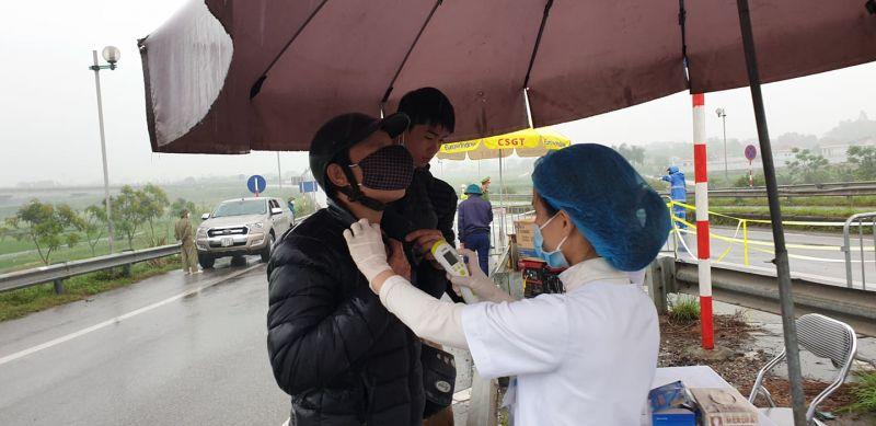 Cán bộ y tế tiến hành đo thân nhiệt cho các tài xế tại chốt số 10, quốc lộ 18 lối xuống đường Võ Văn kiệt để vào HN