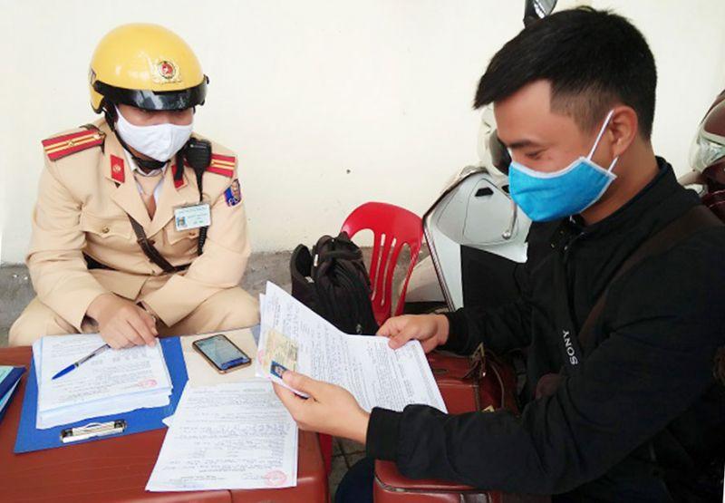 Đại úy Đỗ Xuân Khoa, Đội Cảnh sát giao thông số 6 (Công an thành phố Hà Nội) vừa xử lý lỗi vi phạm giao thông vừa kết hợp tuyên truyền, hướng dẫn người dân về hình thức nộp phạt trực tuyến.