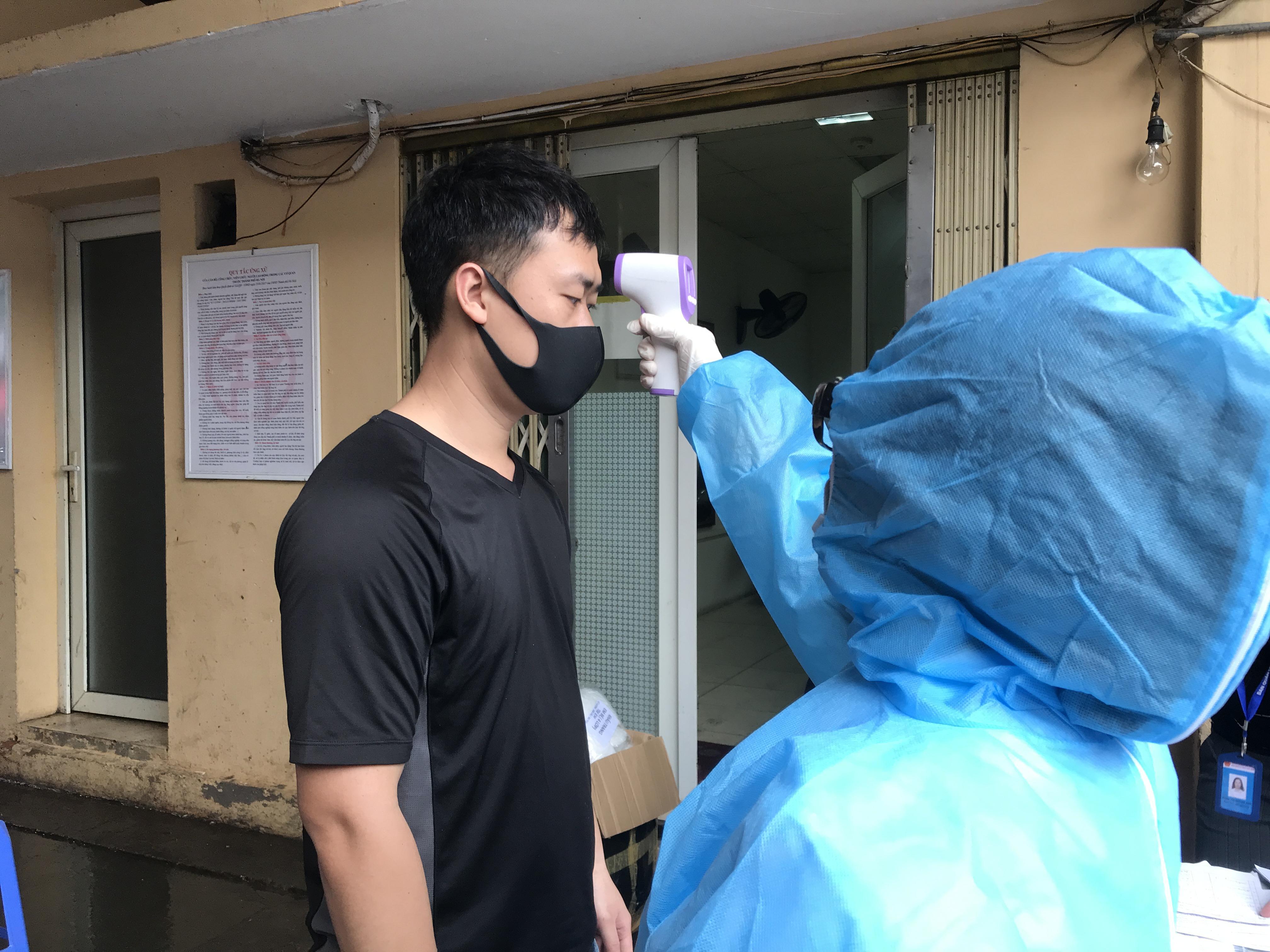 Người dân được đo thân nhiệt trước khi vào xét nghiệm test Covid-19.
