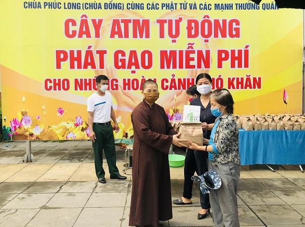 Thầy Thích Đàm Hoài, trụ trì chùa Phúc Long cùng Phó Chủ tịch MTTQ huyện Thanh Trì Nguyễn Thị Thắm trao phát gạo miễn phí cho người dân khó khăn