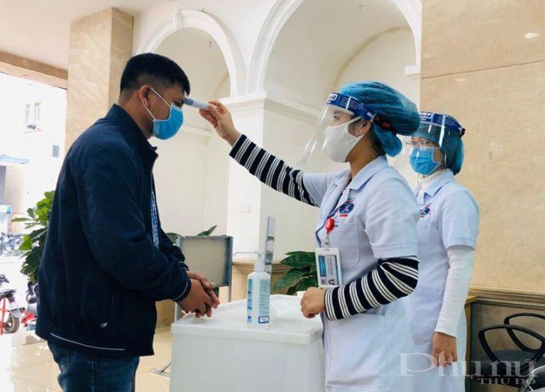 Bệnh nhân và người nhà bệnh nhân được đo thân nhiệt và khám sàng lọc khi đến thăm khám tại BV K Trung ương.