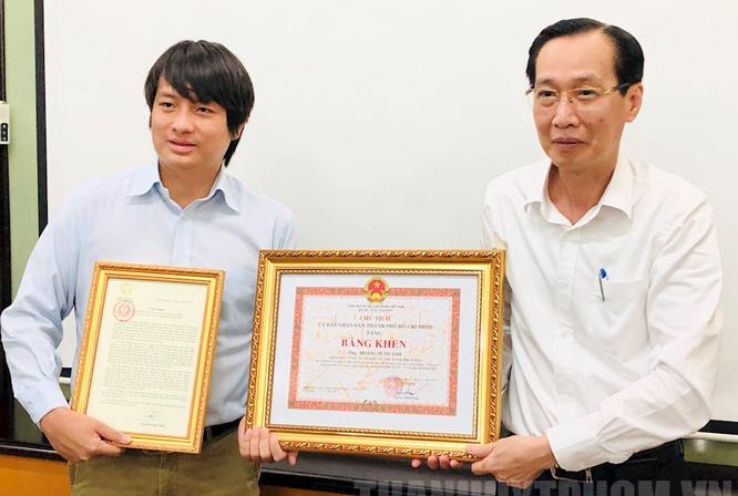 Thừa ủy quyền Phó Chủ tịch nước, Phó Chủ tịch Thường trực UBND thành phố Hồ Chí Minh Lê Thanh Liêm (bên phải) trao Thư khen cho anh Hoàng Tuấn Anh.