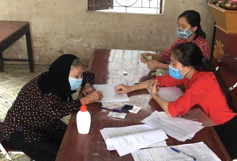 Người dân xã Quang Tiến (huyện Sóc Sơn) nhận tiền hỗ trợ.