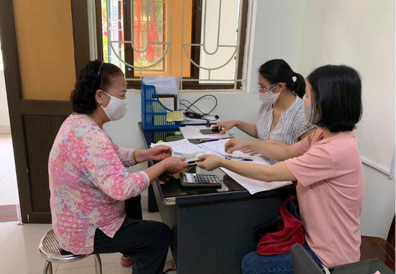 Người dân thị xã Sơn Tây nhận tiền hỗ trợ.