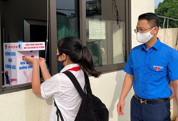 Các em học sinh sát khuẩn tay trước khi vào lớp học