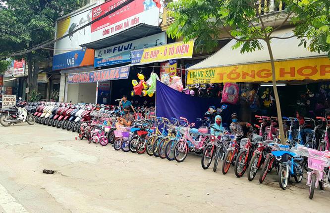 Vỉa hè quốc lộ 21B đoạn qua thị trấn Vân Đình (huyện Ứng Hòa) bị nhiều hộ lấn chiếm để bày bán hàng. Ảnh: Gia Huy