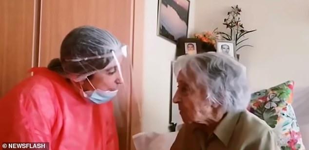 Bà Maria Branyas trò chuyện cùng một người chăm sóc trong bộ đồ bảo hộ