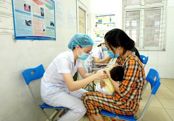 Phụ huynh và trẻ nhỏ đeo khẩu trang để đảm bảo an toàn khi tiêm chủng. Ảnh: Thiện Tâm