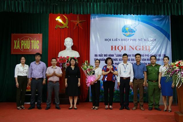Đồng chí Nguyễn Thị Tuyết Mai, Trưởng ban Gia đình -Xã hội, Hội LHPN Việt Nam (thứ 4 từ trái qua) và đồng chí Lê Thị Thiên Hương, Phó Chủ tịch Hội LHPN Hà Nội (thứ 6 từ trái qua) tặng hoa chúc mừng Ban điều hành Mô hình