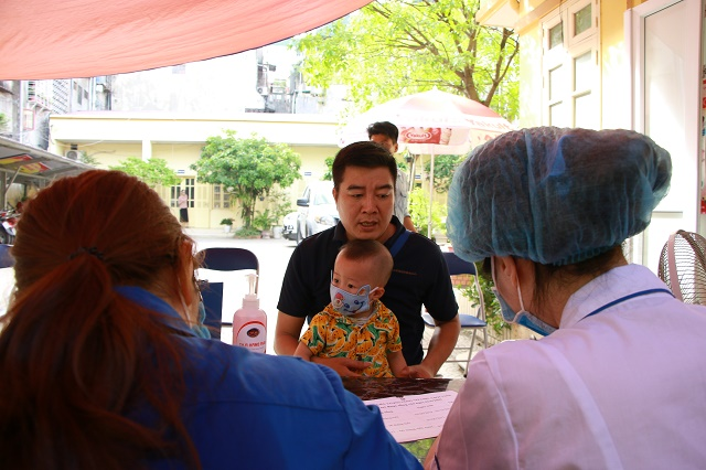 Tại Trạm Y tế phường hàng Bột, quận Đống Đa nhiều ông bố đưa con tới uống Vitamin A và cân đo, đánh giá tình trạng dinh dưỡng.