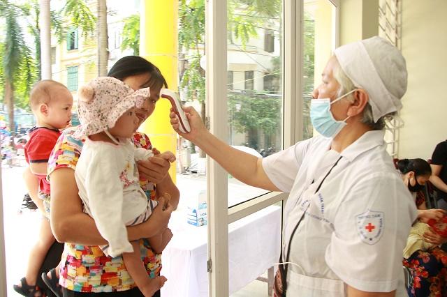 Tại điểm uống Vitamin A đặt tại Nhà văn hóa phường Nhân Chính, quận Thanh Xuân, bà mẹ và trẻ nhỏ đều được kiểm tra thân nhiệt để phòng chống dịch Covid-19. Đây là 1 trong 5 điểm uống Vitamin A trên địa bàn Phường.