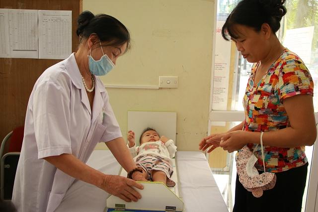 Các cháu nhỏ được nhân viên y tế cẩn thận đo chiều cao .