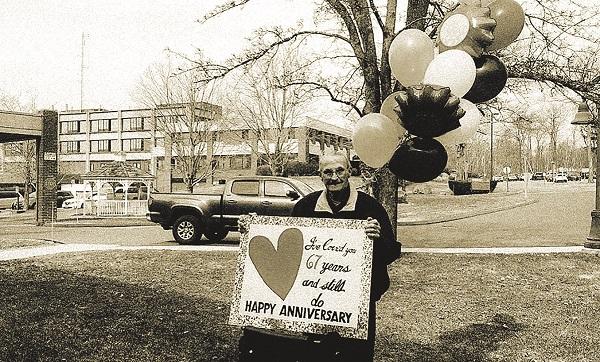 """Ông Bob cùng tấm bảng ghi dòng chữ """"Dù đã trải qua 67 năm, tình yêu mà anh dành cho em vẫn vẹn nguyên như thuở ban đầu"""""""
