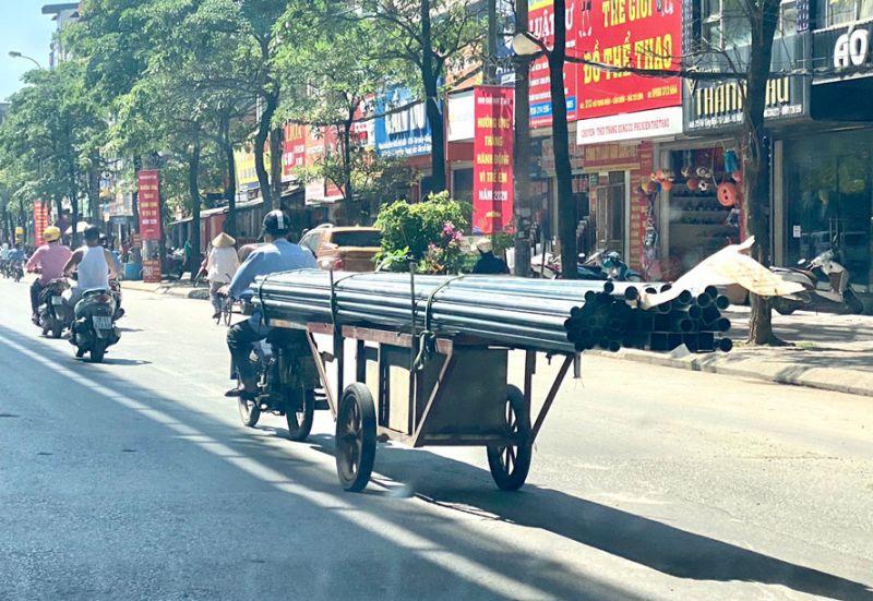 Xe máy cũ ngang nhiên chở hàng cồng kềnh lưu thông trên đường phố của Hà Nội.