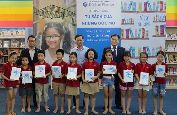 Ông Trần Văn Hà Giám đốc Thư viện Hà Nội và đại diện Ban Giám đốc Shinhan Finance trao quà cho các em học sinh