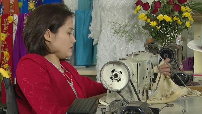 Phạm Thị Thắm bên chiếc máy may của mình.