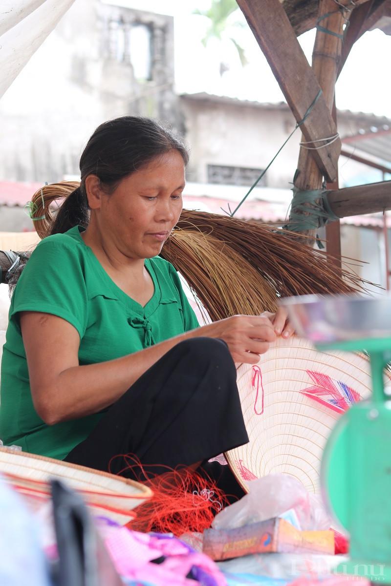 Ảnh 2: Đôi bàn tay khéo léo đan nón của một tiểu thương tại đình làng Chuông. Ảnh: Minh Hiền