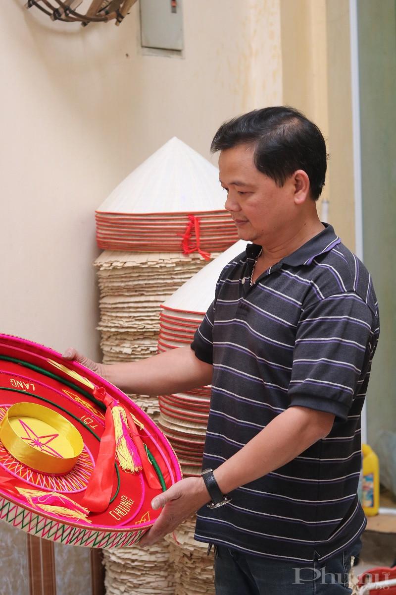 Nghệ nhân Nguyễn Văn Tuy nâng niu chiếc nón quai thao được cách điệu. Ảnh: Minh Hiền