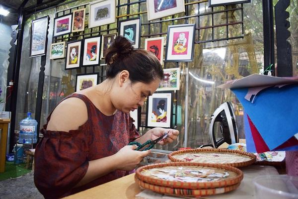 Nhân viên HTX Vụn Art say sưa cắt dán các chi tiết từ vải lụa để tạo thành những bức tranh dân gian độc đáo
