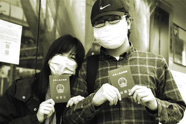 Anh Lu và vợ, cô Đinh khoe giấy chứng nhận kết hôn tại văn phòng đăng ký kết hôn ở Vũ Hán