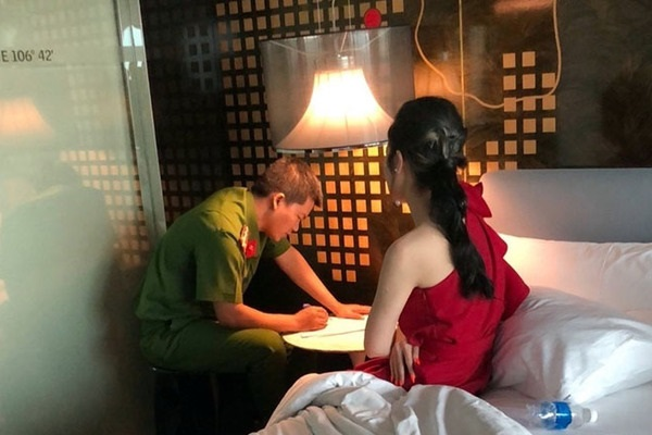 Công an lấy lời khai của một cô gái bán dâm bị bắt quả tang tại khách sạn. (Ảnh: Báo CAND)