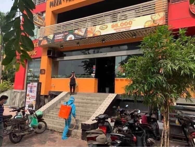 Lực lượng chức năng phun khử khuẩn tại cửa hàng Pizza 106 Trần Thái Tông, Cầu Giấy.