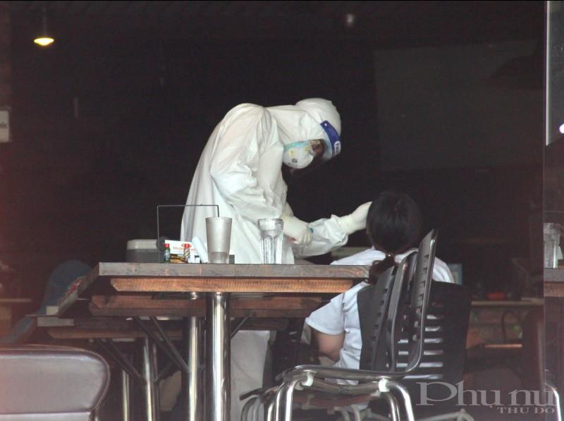 Cán bộ y tế lấy mẫu xét nghiệm trường hợp tiếp xúc gần với ca nghi nhiễm tại Hà Nội.
