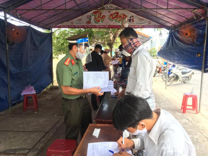 Người dân tiến hành khai báo y tế tại trạm kiểm soát trước khi vào TP. Hội An.