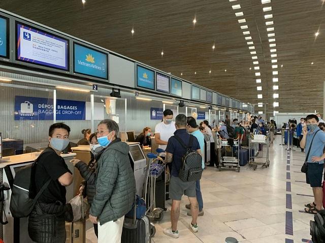Hành khách đang làm thủ tục tại sân bay để về Việt Nam.