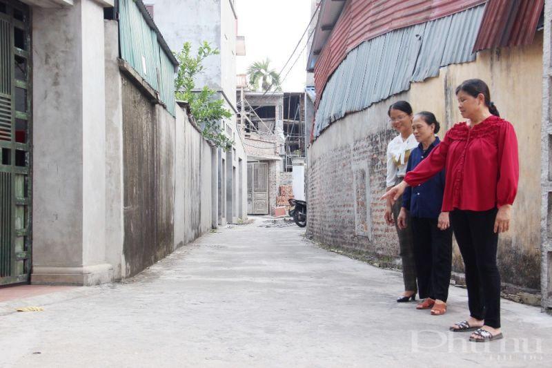 Chị Cao Thị Tĩnh (áo đỏ) cho biết, nơi chị đứng trước kia là đường đất, chỉ rộng 2m2 nhưng nay đã được bê tông hóa kiên cố và mở rộng lòng đường nhờ bà con hiến đất.