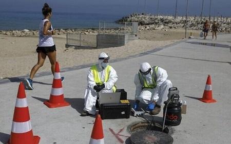 Các kỹ thuật viên từ công ty Kando trích xuất các mẫu nước thải từ một hố ga gần bãi biển ở thành phố Ashkelon - Ảnh: AFP