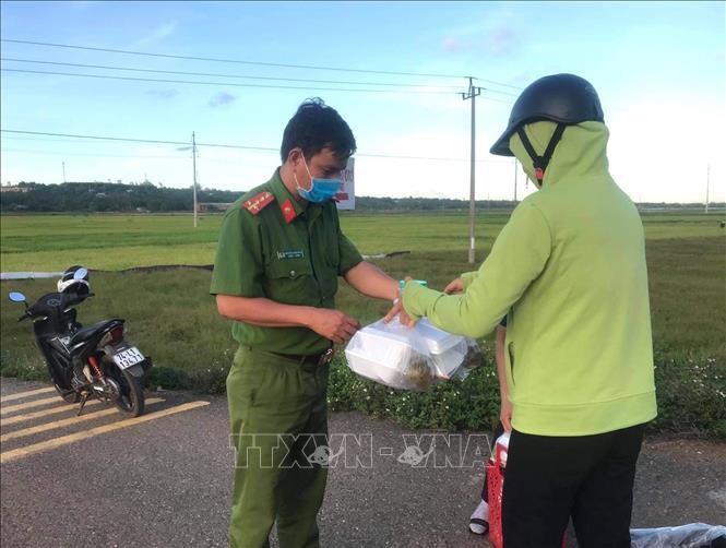 Người dân xã Vĩnh Hòa trao những suất ăn, hỗ trợ lực lượng làm nhiệm vụ phong tỏa thôn Đơn Duệ. Ảnh: TTXVN phát