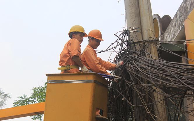 Công nhân EVN Hà Nội thanh thải đường dây điện tại phố Đội Cấn (quận Ba Đình), ảnh chụp năm 2019. Ảnh: Đỗ Tâm