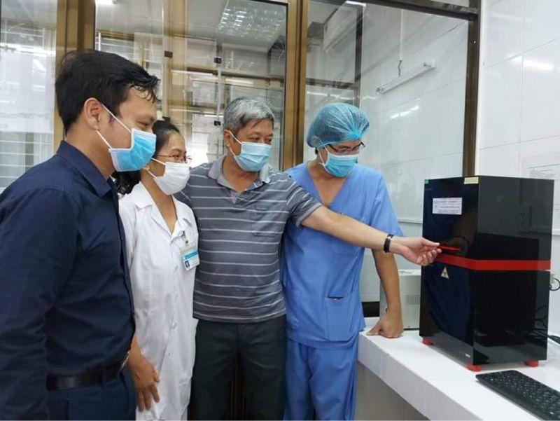 Thứ trưởng Bộ Y tế Nguyễn Trường Sơn và các chuyên gia kiểm tra hệ thống thiết bị xét nghiệm trong ngày đầu khai trương.