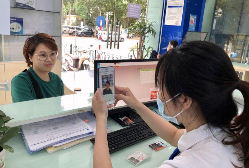 Nhân viên VinaPhone tại Hà Nội thực hiện chụp ảnh bằng AI sinh trắc học để đăng ký thông tin cho khách hàng.