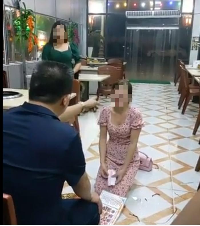 Cô gái vừa quỳ vừa khóc do bị đe dọa (ảnh: Cắt từ clip)