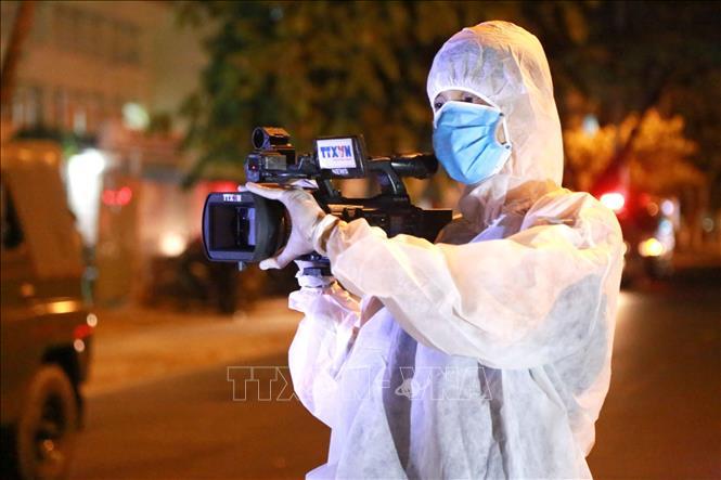 Quay phim Viết Đức (Truyền hình Thông tấn Vnews) tác nghiệp trong khu vực bị phong tỏa tại Đà Nẵng. Ảnh: Quốc Dũng/TTXVN