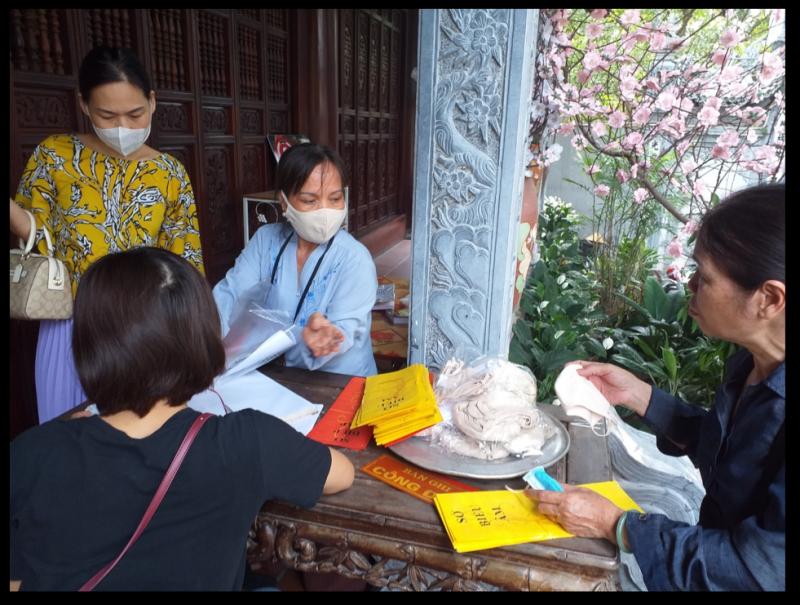 Người dận được yêu cầu sát khuẩn tay và nhận khẩu trang miễn phí trước khi vào lễ tại chùa Vạn Niên