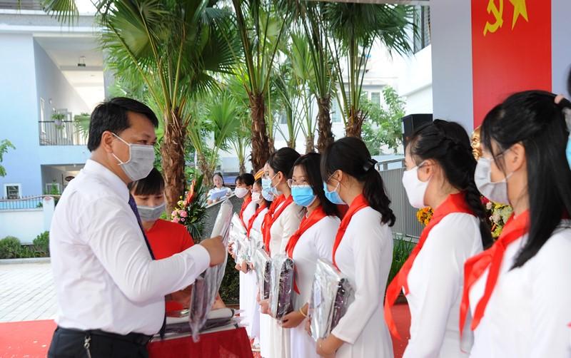 Nữ sinh  lớp 9, trường THCS Kim Giang mặc áo dài, được lãnh đạo quận Thanh Xuân tặng cặp sách