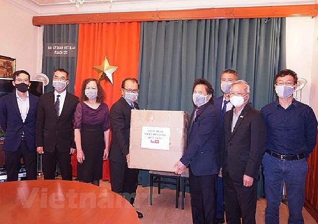 Trao tặng khẩu trang y tế cho cộng đồng người Việt.(Nguồn: Vietnam+)