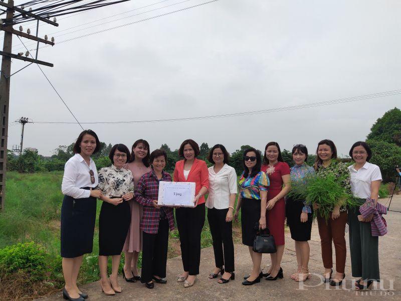 Các đại biểu tặng quà cho cán bộ chi hội phụ nữ thôn Kim Quan xã Yên Viên  đơn vị giới thiệu mô hình trồng măng tây an toàn tại xã