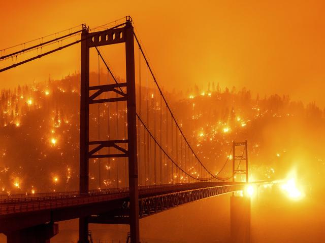 Than nóng đỏ từ vụ cháy thắp sáng cả một sườn đồi phía sau cây cầu Bidwell Bar